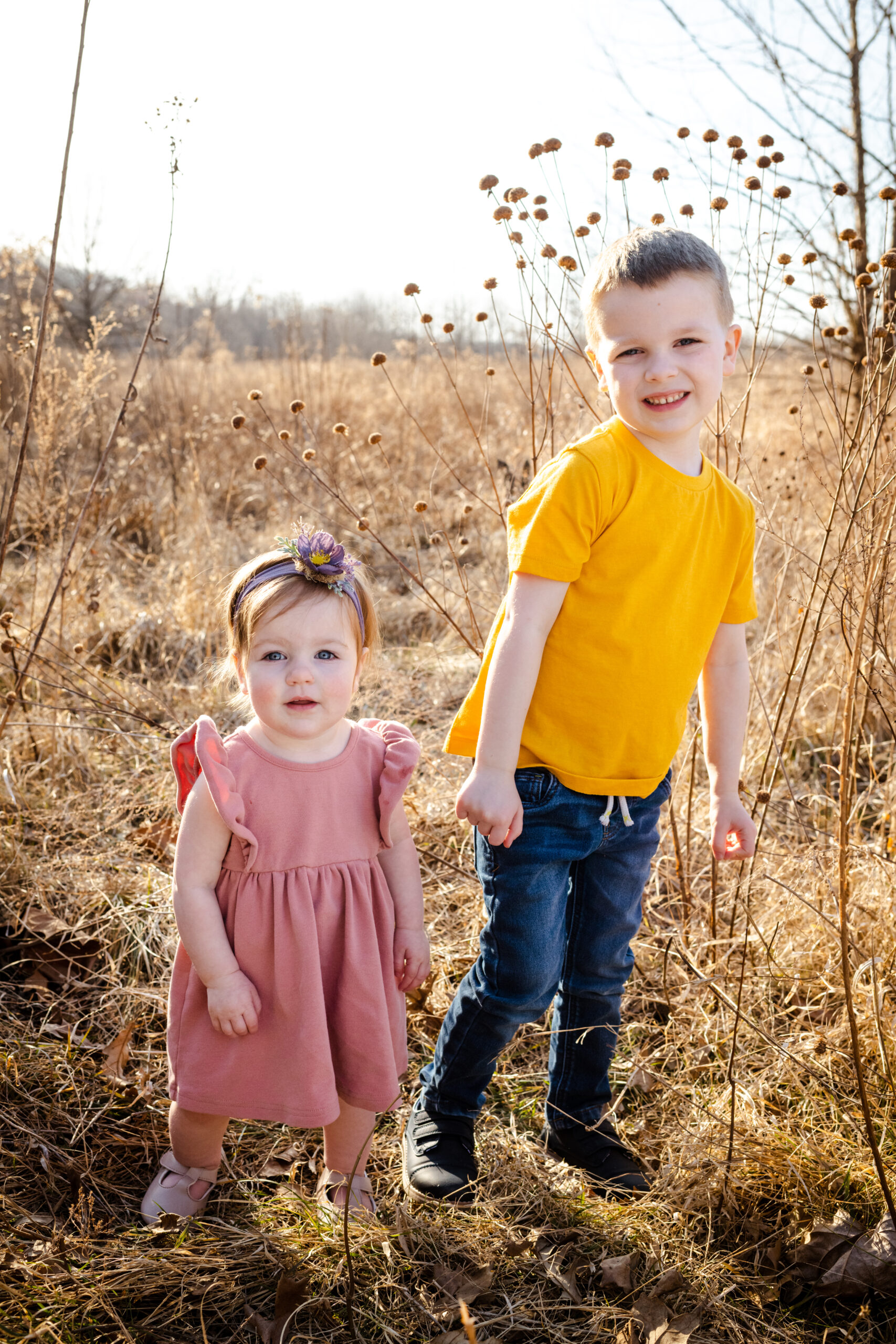 brother standing by little sister in golden field