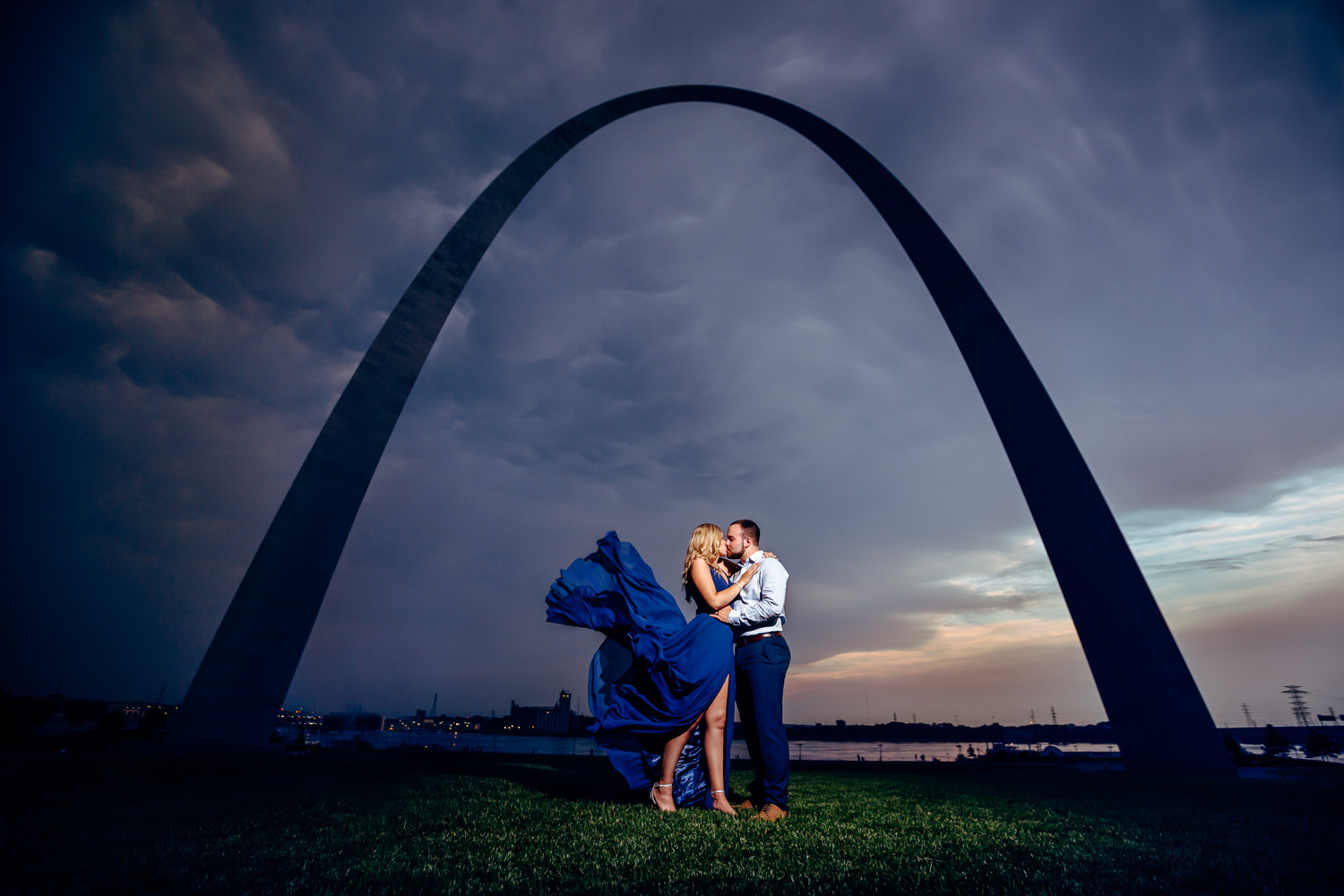 Engaged couple kissing under St. Louis Arch with dress flying