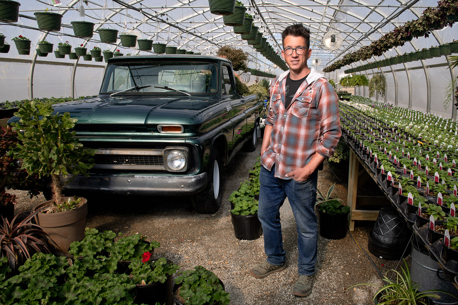 Greenhouse owner stands by old green truck in Callaway Fields Greenhouse