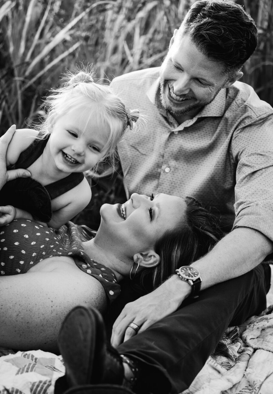 husband and wife laughing with daughter